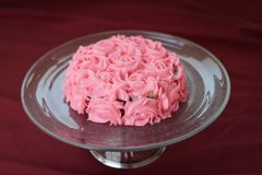 Dekorerade rosa Rose Frosting Cake On en Glass platta arkivfoto