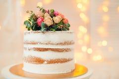 Dekorerat av den vita nakna kakan för blommor, lantlig stil för bröllop, födelsedagar och händelser Arkivfoton