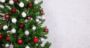 Dekorerat julträd med färgrika bollar över den vita tegelstenwaen royaltyfri fotografi