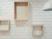 Dekorujący biały ściana z cegieł z drewnianymi pudełkami w różnorodnych rozmiarach i część lekka lampa Obrazy Stock