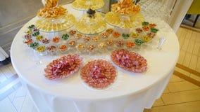 Dekorujący cateringu bankieta stół z układami scalonymi, dokrętkami i różnym jedzeniem, zdjęcie wideo