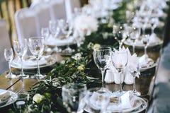 Dekorujący elegancki drewniany ślubu stół w wieśniaka stylu z eukaliptusem, kwiaty, porcelana talerze i szkła, zdjęcie royalty free