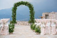 Dekorujący krzesła przy ślubnym miejscem wydarzenia i łuk Obrazy Stock