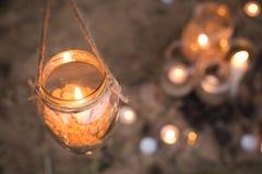 Dekorujący romantyczny miejsce dla daty z słojami świeczki hunging na drzewie i pozyci na piasku pełno kosmos kopii Zdjęcia Stock