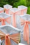 Dekorujący krzesła dla gości przy ślubem w ogródzie Obrazy Royalty Free