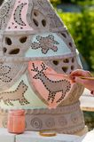 Dekoruje glinianą wazę i glazuruje zanim ono piec na ogieniu Kobiety ręka z muśnięciem niesie barwionego glazerunek na amforze zdjęcia royalty free