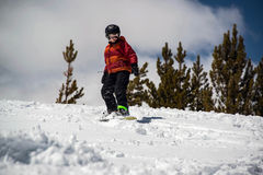 Del adolescente de la snowboard colina nevosa escarpada abajo en las montañas Imagenes de archivo