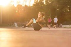 Del adolescente del ABS del ejercicio puesta del sol joven del día soleado al aire libre Fotos de archivo