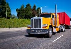 Del aparejo camión grande anaranjado clásico semi con el envase rojo en cama plana Imagenes de archivo