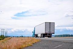 Del aparejo camión grande azul semi que conduce con semi el remolque en el ascendente imagen de archivo