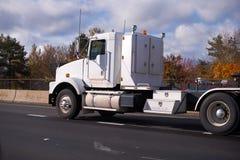 Del aparejo camión grande clásico semi con la unidad de almacenamiento y la cama plana traile Fotografía de archivo libre de regalías