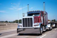 Del aparejo camión grande clásico semi en remolque de la cama rojo oscuro y plana semi Fotos de archivo