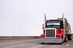 Del aparejo camión grande negro y rojo clásico potente semi que transporta r fotografía de archivo