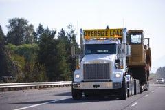 Del aparejo camión grande semi con la muestra de gran tamaño de la carga y el remolque descender Foto de archivo libre de regalías