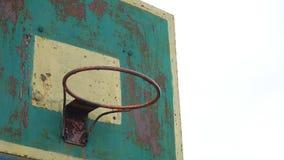 Del aro del baloncesto de la parte inferior del deporte de la opinión la bola oxidada vieja del hierro al aire libre entra en la  almacen de metraje de vídeo