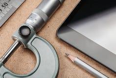 Del av arbetsplatsen med minnestavlan, linjalen, blyertspennan och mikrometer Royaltyfri Foto
