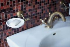 Del av badrum - tvättställ med bronskranen, vit kugge för tvål, brun bakgrund för mosaiktegelplatta Suddig bild arkivfoton
