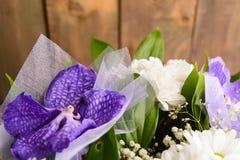 Del av buketten med orkidén på träbakgrund Royaltyfri Foto