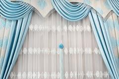 Del av den beautifully draperade gardinen på fönstret i rummet Slut upp av gardingardin med hängear Lyxig gardin, hem- deco Royaltyfri Bild