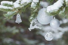 Del av den dekorerade julgranen med djura Jultomte struntsaker för för renprydnad och silver på snöig filialer Arkivbilder