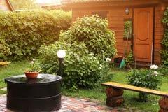 Del av den formella trädgården med fotoet för sommar för ställe för skjulbänkgrillfest Royaltyfria Foton