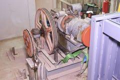 Del av den industriella elevatorn Blockhjul och motor i maskinrum Rekonstruktion av den industriella elevatorn Royaltyfri Foto