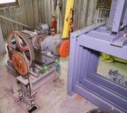 Del av den industriella elevatorn Blockhjul och motor i maskinrum Rekonstruktion av den industriella elevatorn Arkivbilder
