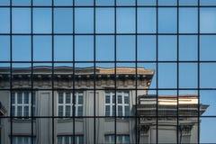 Del av den judiska historiska institutbyggnaden i Warszawa, Polen, reflekterad i den glass fasaden av den moderna byggnaden mitt  royaltyfri bild
