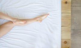 Del av den kvinnliga kroppen på sängen arkivfoto