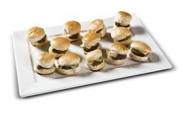Del av den mini- hamburgaren med ost Vit bakgrund Royaltyfria Bilder