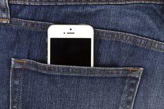 Del av den mobila vita mobiltelefonen i bakfickan av blå grov bomullstvill Royaltyfri Foto
