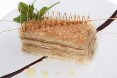 Del av den s?ta klassiska i lager kakan av Napoleon p? en ljus bakgrund royaltyfri foto