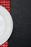 Del av den tomma plattan på en rutig servett, svart bakgrund royaltyfria foton