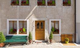 Del av det härliga huset med röda blommor på fönstren Royaltyfri Fotografi