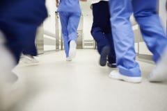 Del av doktorer som kör till och med korridoren i sjukhus fotografering för bildbyråer