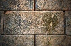 Del av en gammal och smutsig riden ut tegelstenvägg i rött och brunt arkivfoto
