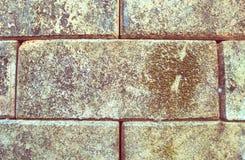 Del av en gammal och smutsig riden ut tegelstenvägg i rött och brunt royaltyfri bild