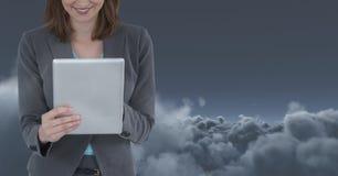 Del av en kvinna som framme använder en digital minnestavla av ett mörkt moln Arkivbild