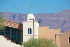 Del av en kyrklig byggnad med ett kors och berg i bakgrunden royaltyfri foto