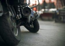 Del av en splitterny motorcykel med hjul och ett smutsigt avgasrörrör arkivbild