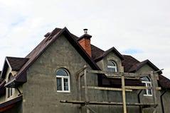 Del av ett grått nytt oavslutat hus mot himlen royaltyfri bild