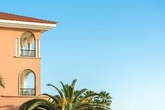 Del av ett lyxigt hus i medelhavs- stil med palmträd och kopieringsutrymme i den blåa himlen arkivbilder
