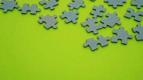 Del av ett pussel på en grön bakgrund Arkivfoto