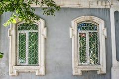 Del av fasaden av ett grått gammalt stenhus med två fönster i vita platbands Royaltyfri Bild
