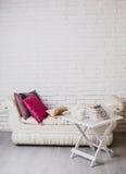 Del av inre med soffan och dekorativa kuddar, vit trätabell med böcker på den Royaltyfri Foto