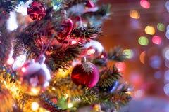 Del av julgranen, med färgrika glass bollar, små garneringar och färgrika ljusa reflexioner Royaltyfria Bilder