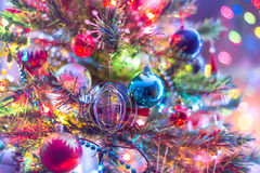 Del av julgranen, med färgrika glass bollar, små garneringar och färgrika ljusa reflexioner Arkivbild