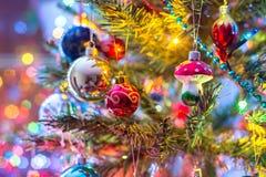 Del av julgranen, med färgrika glass bollar, små garneringar och färgrika ljusa reflexioner Arkivfoton