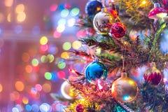 Del av julgranen, med färgrika glass bollar, små garneringar och färgrika ljusa reflexioner Royaltyfri Foto