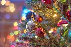 Del av julgranen, med färgrika glass bollar, små garneringar och färgrika ljusa reflexioner Royaltyfri Bild